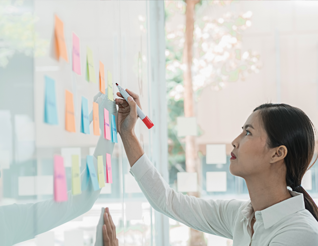 Young Asian woman about to write on a whiteboard with many colours of post its