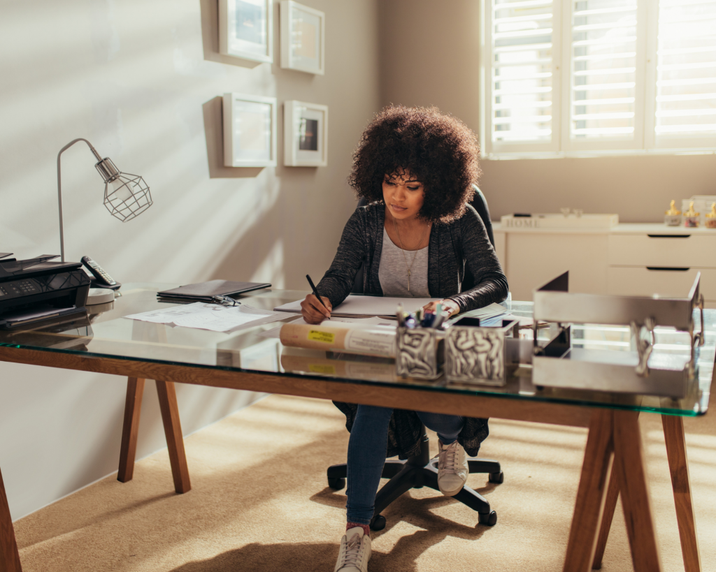 Woman of colour sitting at a large desk writing notes