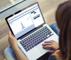 A women sitting looking at a computer screen showing the fundraisingManager homescreen on the Salesforce platform